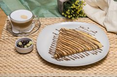 Folded crepe, Russian blini with chocolate sauce on white plate with cappuccino and dragees with fabric pouch and yellow flowers. Folded crepe, Russian blini stock photos