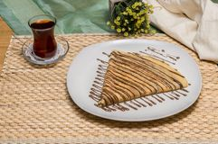 Folded crepe, Russian blini with chocolate sauce on white plate served with Turkish tea with fabric pouch and yellow flowers. Folded crepe, Russian blini with royalty free stock photography