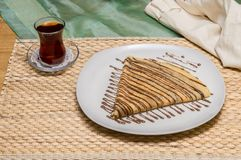 Folded crepe, Russian blini with chocolate sauce on white plate served with Turkish tea. Folded crepe, Russian blini with chocolate sauce on a white plate served royalty free stock photography