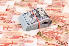 Folded dollar bills wrapped by rubber band over banknotes. Of russian rubles Royalty Free Stock Photo