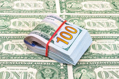 Folded dollar bills wrapped by rubber band over dollars Royalty Free Stock Image