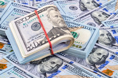 Folded dollar bills wrapped by rubber band over dollars Royalty Free Stock Images