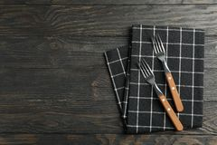 Folded fabric napkin with forks on wooden background, top view stock photo