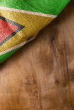 Folded flag of Guyana. On a wooden background Stock Image