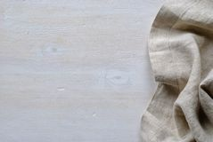 Folded and gathered linen fabric side border. In a neutral weave over textured white painted wood with copy space stock photography