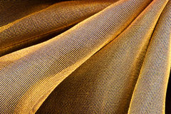Folded golden fabric Stock Images