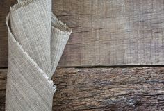 Folded gray napkin on a wooden background. Burlap texture. Pattern fabric textile. Texture background Stock Photography