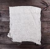 Folded gray towel on brown wooden background. Top view stock images