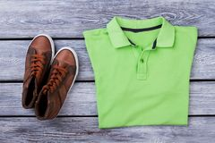 Folded green polo shirt and brown sneakers. Wooden desk surface background Stock Image