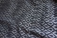 Folded grey fabric with black diamonds pattern Royalty Free Stock Photos