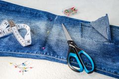 Folded in half blue jeans with large hole on pant leg below the knee, sewing pins, tailor tape and scissors. Folded in half blue jeans with large hole on pant stock photography