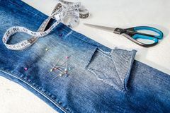 Folded in half blue jeans with a large hole on pant leg below the knee, sewing pins, tailor tape and scissors. Folded in half blue jeans with a large hole on stock image