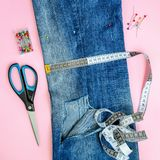 Folded in half blue jeans with large hole on pant leg, sewing pins, tailor tape and scissors. Folded in half blue jeans with large hole on pant leg, multi stock photo