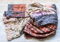 Folded silk patchwork scarf on wooden table stock photo