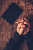 Folded hands of Christian man praying. With Holy Bible by his side on wooden desk in church, top view stock photo