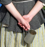 Folded hands. Of colonial woman holding a tin cup Stock Photos