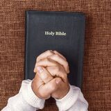 Folded hands of the man in the holy bible