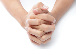 Folded hands praying. Close-up frontal top view of two hands folded with intertwined fingers praying on a white desktop Stock Image