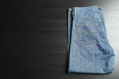 Folded jeans on black table royalty free stock photography