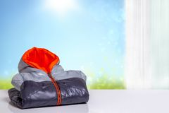 Free Folded Kids Colorful Autumn Jacket. A Colorful Warm Down Jacket With Orange Lining On A White Table Over Abstract Light Blue Sunny Stock Photos - 134868553