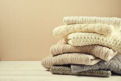 Folded pastel sweaters on white wooden table Stock Photos