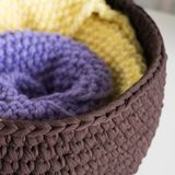 Folded knitted blankets in the basket royalty free stock photo