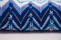Folded knitted cotton sweater with zigzag pattern on white background Royalty Free Stock Photo