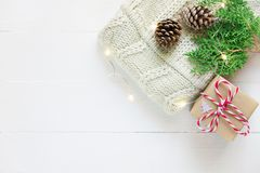 Folded knitted off-white wool sweater gift box pine cones green juniper twig golden lights garland on plank wood table. Christmas. Folded knitted off-white wool royalty free stock images