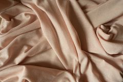 Folded beige polyester textile with sparkling fiber. Folded light beige polyester textile with sparkling fiber Stock Photos