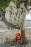 Folded linen beach umbrellas in evergreen tamarisks shade on Greek sandy autumn beach near Mastihari bay on Kos island Stock Image