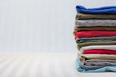 Folded mens clothing on stripy background Royalty Free Stock Photography