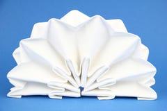 Folded napkin. On the blue background royalty free stock images