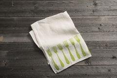 Folded Napkin with Green Fork Pattern on Wooden Surface Royalty Free Stock Images