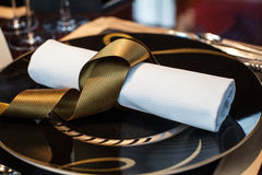 Folded napkin laid on plate on the table at restaurant Stock Image