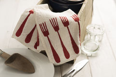 Folded Napkin with Red Fork Pattern Hanging on Wooden Box Stock Images