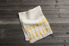 Folded Napkin with Yellow Fork Pattern on Wooden Surface Stock Photo