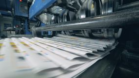 Folded newspaper on an automated belt, typographical machine. 4K stock footage