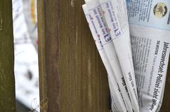 Folded newspaper clamped between pickets of a wooden fence Royalty Free Stock Photography