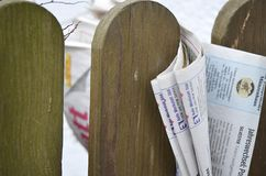 Folded newspaper clamped between pickets of a wooden fence Stock Photo