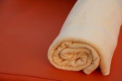 Folded orange bath towel on orange background Royalty Free Stock Images