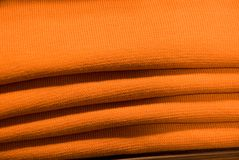 Folded orange sweatshirts Stock Images