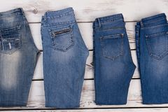 Folded pairs of jeans. On wooden background. Jeans obsession, sale of urban American outlet apparel Stock Image