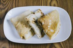 Folded pancake in a plate on a wooden background malaysian delicacies Royalty Free Stock Image