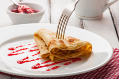 Folded pancake on white plate. Light summer breakfast with hot pancake and raspberry jam Stock Photography