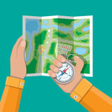 Folded paper city map and compass in hands Stock Photo