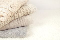 Folded pastel sweaters on white rug background. Text space Stock Photo