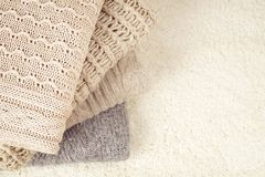 Folded pastel sweaters on white wooden background. Text space Stock Image
