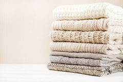 Folded pastel sweaters on white wooden background. Text space Royalty Free Stock Images