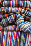 A folded pile of colorful cloth. With different woven patterns Royalty Free Stock Images