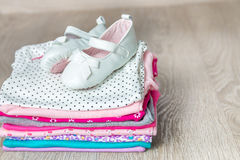 Folded pink and white bodysuit with shoes on it  grey wooden background. diaper for newborn girl. Stack of infant clothing. Child Stock Image
